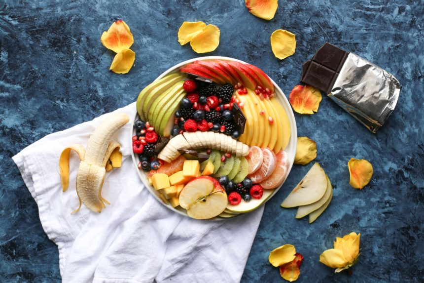 BOWL OF FRUIT WITH BANANAS, APPLES, BLUEBERRIES, RASPBDERRIES, PINEAPPLE, CHEESE ON A WHITE TOWEL WITH BLUE BACKGROUND