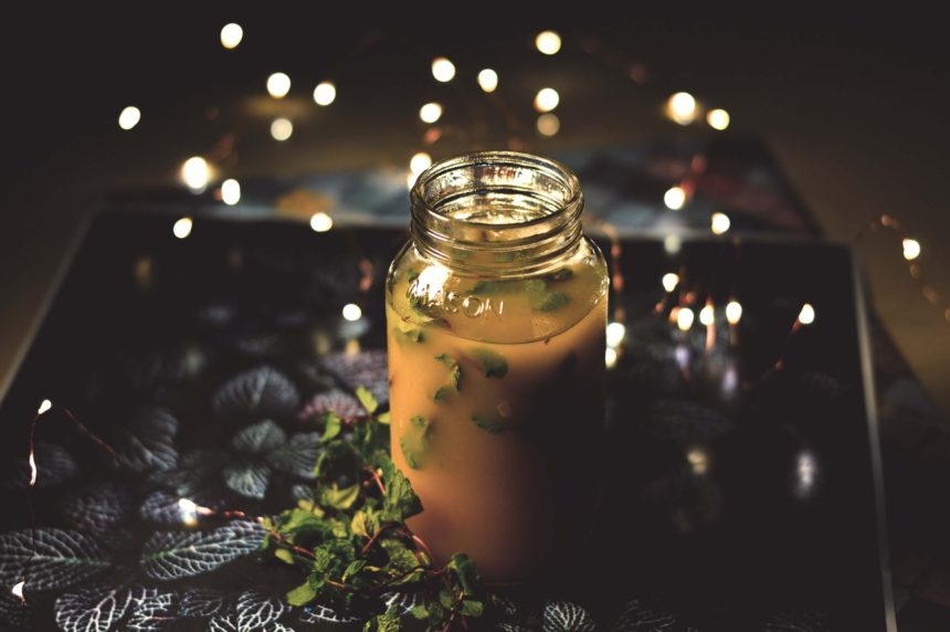 Bone broth in a jar on tray with leaves, tiny lights