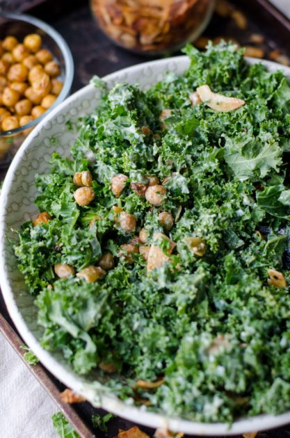 Kale salad with nuts in a white bowl