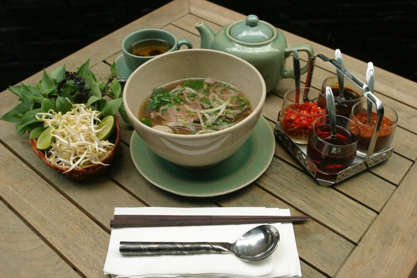 miso soup in a white bowl on table with condiments and silverware on white napkin