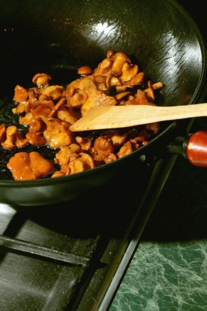 mushrooms cooking in a black frying pain